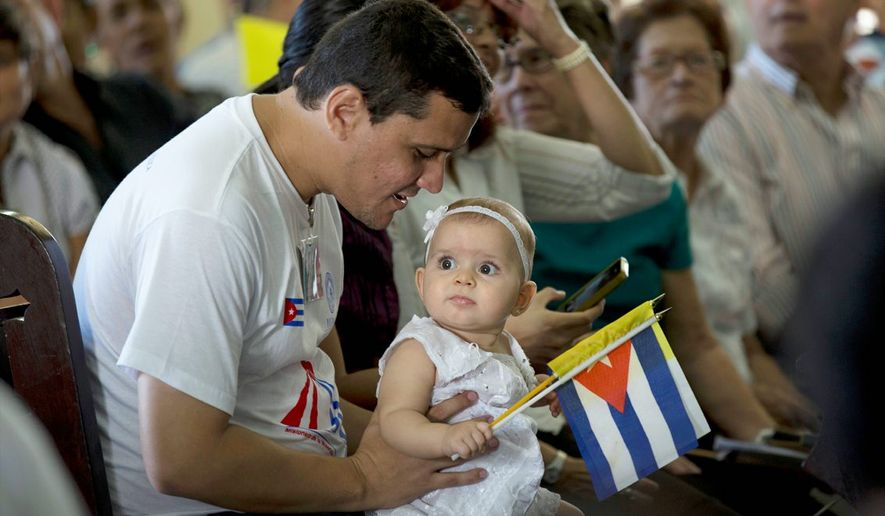 A child holds Cuban and Vatican flags during an homily by Pope Francis at the sanctuary of the Virgin of Charity in El Cobre, in Santiago,  Cuba, Tuesday, Sept. 22, 2015. (Ismael Francisco/Cubadebate via AP)