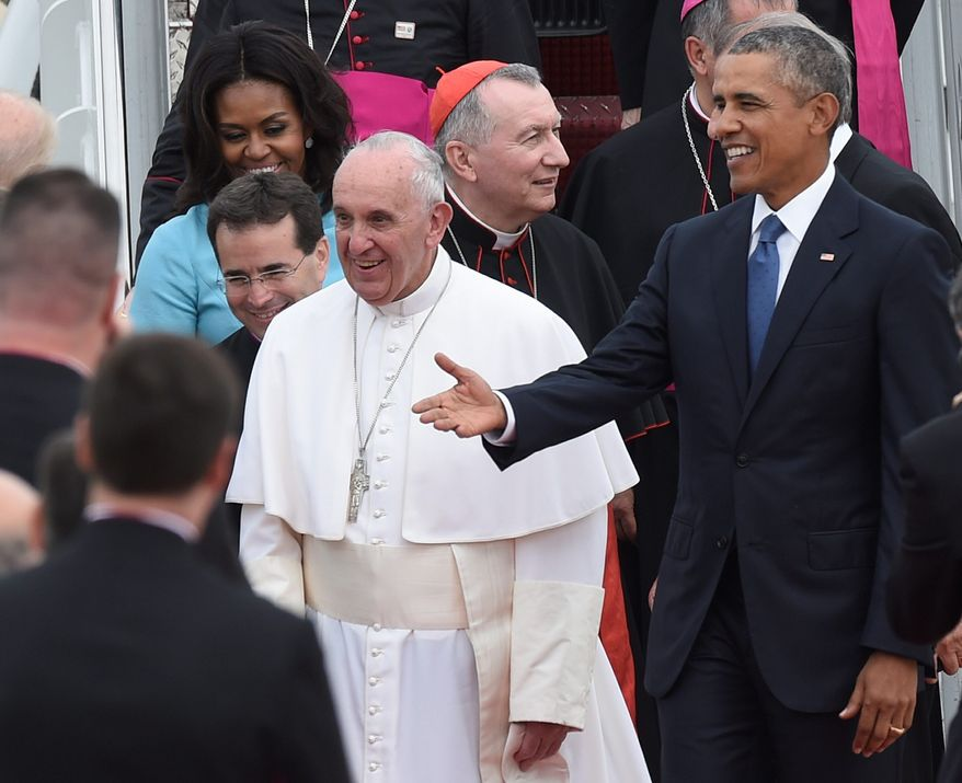 Pope Francis greets people as he is escorted by President Barack Obama after arriving at Andrews Air Force Base in Md., Tuesday, Sept. 22, 2015. The Pope is spending three days in Washington before heading to New York and Philadelphia. This is the Pope's first visit to the United States. (AP Photo/Susan Walsh)