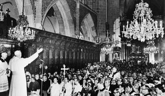 In Poland, Pope John Paul II raises his arms to his audience in the Krakow Wawel Cathedral where the Pontiff celebrated a Mass shortly after he arrived here from Czestochowa, June 7, 1979.  (AP Photo)