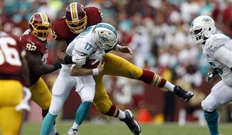 Miami Dolphins quarterback Ryan Tannehill (17) is sacked by Washington Redskins defensive end Jason Hatcher (97) during the first half of an NFL football game Sunday, Sept. 13, 2015, in Landover, Md. (AP Photo/Patrick Semansky)