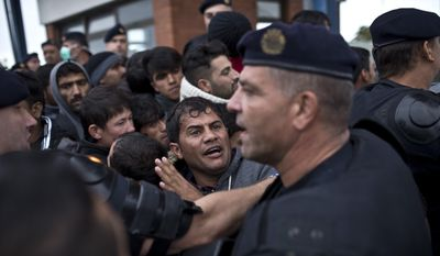 A man reacts as he gets pushed back by Croatian police officers in Opatovac, Croatia, Tuesday, Sept. 22, 2015. Scuffles have broken out between Croatian police and asylum-seekers after they were barred from entering a newly opened reception center meant to register those seeking sanctuary in Europe. (AP Photo/Marko Drobnjakovic)