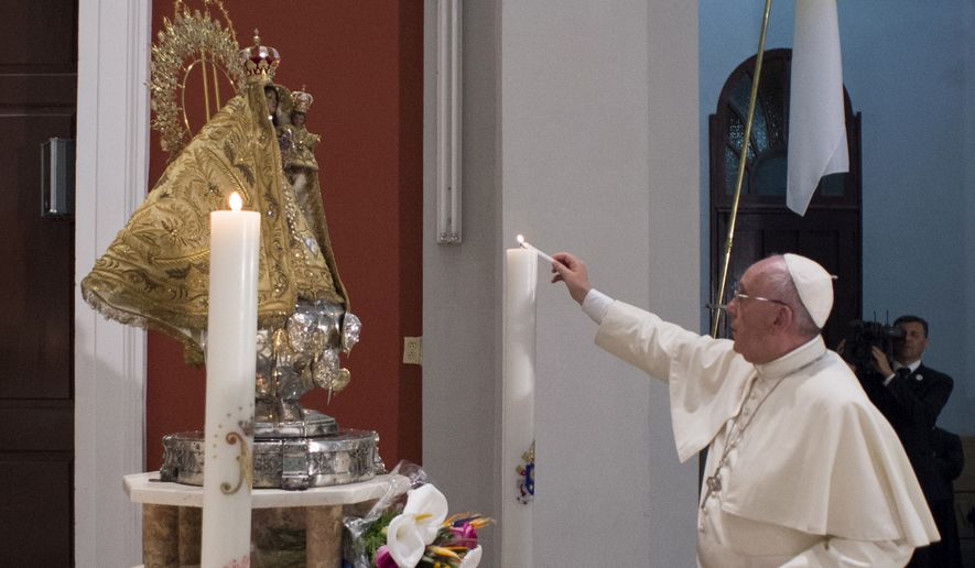In this photo taken on Monday, Sept. 21, 2015, Pope Francis lights a candle during his visit at the sanctuary of the Virgin of Charity of Cobre, in El Cobre, Cuba. Francis arrived in the sanctuary shortly after landing in the nearby eastern city of Santiago, his final stop in Cuba before heading to the U.S. (L'Osservatore Romano/Pool Photo via AP)