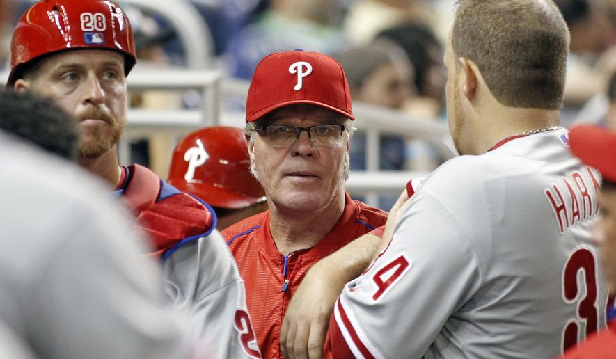 Philadelphia Phillies manager Pete Mackanin, center, speaks with starting pitcher Aaron Harang, right, and catcher Erik Kratz (28) in the third inning of play against the Miami Marlins during a baseball game in Miami, Tuesday, Sept. 22, 2015. (AP Photo/Joe Skipper)