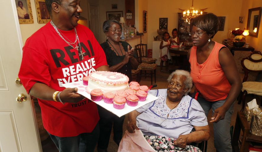"FILE- In this July 25, 2015, file photo, Terrance Jackson, left, Doris Ware, second from left, and Beverly Booker, right, sing ""Happy Birthday To You""  to Bernice Williams, seated, as she celebrates her 103rd birthday in the Mill City neighborhood of Dallas. The music publishing company that has been collecting royalties on the song ""Happy Birthday To You"" for years does not hold a valid copyright on the lyrics to the tune that is one of the mostly widely sung in the world, a federal judge ruled Tuesday, Sept. 22, 2015 (Michael Ainsworth/The Dallas Morning News via AP, File) MANDATORY CREDIT; MAGS OUT; TV OUT; INTERNET USE BY AP MEMBERS ONLY; NO SALES"