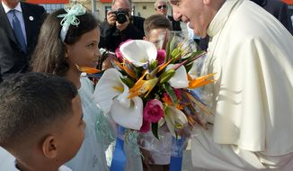 In this photo taken on Monday, Sept. 21, 2015, children greet Pope Francis with flowers upon his arrival at Santiago de Cuba's airport, Cuba. Pope Francis began a 10-day trip to Cuba and the United States on Saturday, embarking on his first trip to the onetime Cold War foes after helping to nudge forward their historic rapprochement. (L'Osservatore Romano/Pool Photo via AP)