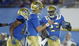 UCLA running back Nate Starks, right, celebrates scoring a touchdown with UCLA quarterback Josh Rosen, center, and wide receiver Eldridge Massington, left, against BYU late in the fourth quarter of an NCAA college football game, Saturday, Sept. 19, 2015, in Pasadena, Calif. UCLA won 24-23. (AP Photo/Danny Moloshok)