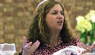 In this Sept. 5, 2015 photo, interim rabbi Rebecca L. Dubowe speaks to a group during a Torah reading and Bible study at the Moses Montefiore Temple  Bloomington, Ill. Dubowe is believed to be the first deaf, female rabbi to be ordained in the world, but she is not defined by that title. Her colleagues say her passion for Judaism and her connection with others is what makes her a strong leader in the temple. (Steve Smedley/The Pantagraph via AP)