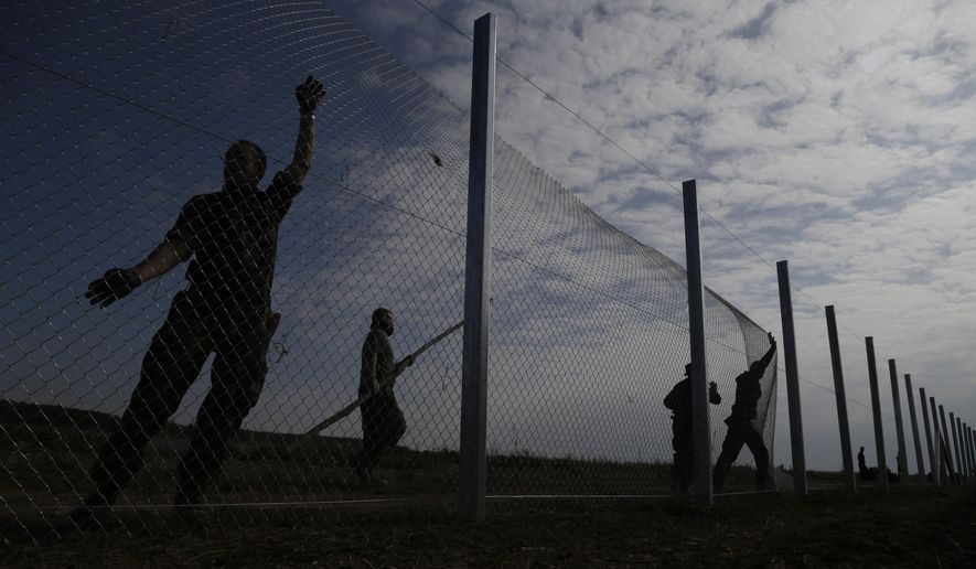 "Hungarian soldiers work on a fence that is being built at the border with Croatia, near the village of Beremend, Hungary, Tuesday, Sept. 22, 2015. Hungary's prime minister Viktor Orban said that millions of migrants are ""laying siege"" to the borders of his country and of Europe, putting the continent in danger. (AP Photo/Petr David Josek)"