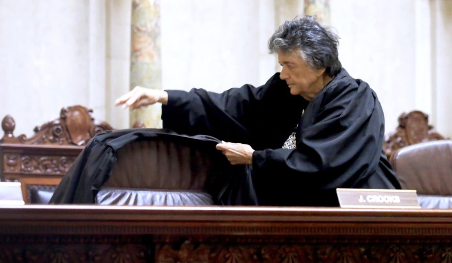 Wisconsin Supreme Court Justice Shirley Abrahamson places a judicial robe on the chair of the late Justice N. Patrick Crooks following a moment of silence in the court in the Wisconsin State Capitol in Madison, Wis. Tuesday, Sept. 22, 2015. Crooks died unexpectedly in his chambers on Monday afternoon.  (John Hart/Wisconsin State Journal via AP) MANDATORY CREDIT