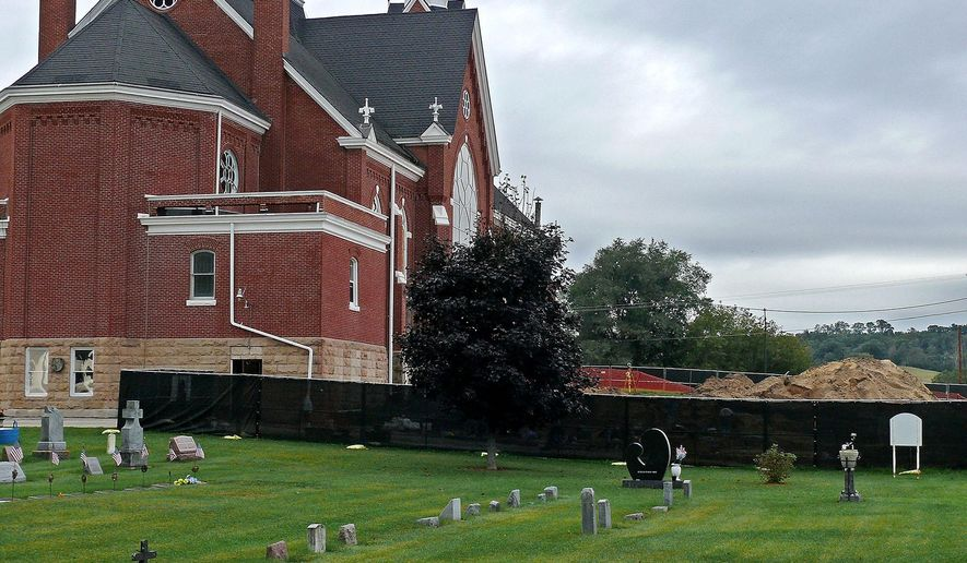 A combination mesh and cyclone fence prevents onlookers from viewing the exhumation of remains, Tuesday, Sept. 22, 2015 at more than 100 burial sites on the north side of Ss. Peter and Paul Catholic Church in Independence, Wis.  The remains and artifacts will be removed, stored and later reburied at a nearby location once a building restoration project is completed.  (Chuck Rupnow/Eau Claire Leader-Telegram via AP)