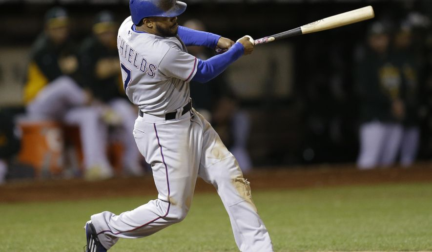 Texas Rangers' Delino DeShields swings for an RBI sacrifice fly off Oakland Athletics' Drew Pomeranz during the sixth inning of a baseball game Tuesday, Sept. 22, 2015, in Oakland, Calif. (AP Photo/Ben Margot)