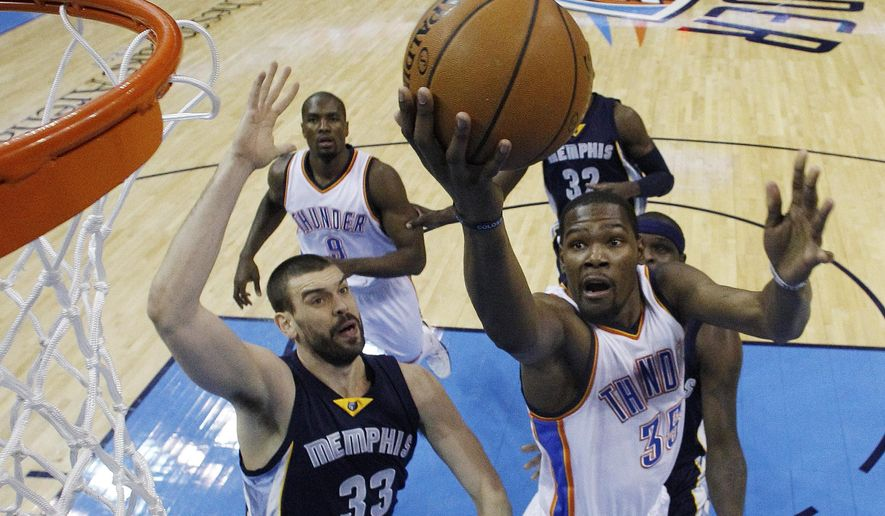 FILE - In this Feb. 11, 2015, file photo, Oklahoma City Thunder forward Kevin Durant (35) shoots in front of Memphis Grizzlies center Marc Gasol (33) during the first quarter of an NBA basketball game in Oklahoma City. Durant has been cleared to play without restriction after recovering from a foot injury, general manager Sam Presti said Wednesday, Sept. 23, 2015. (AP Photo/Sue Ogrocki, File)