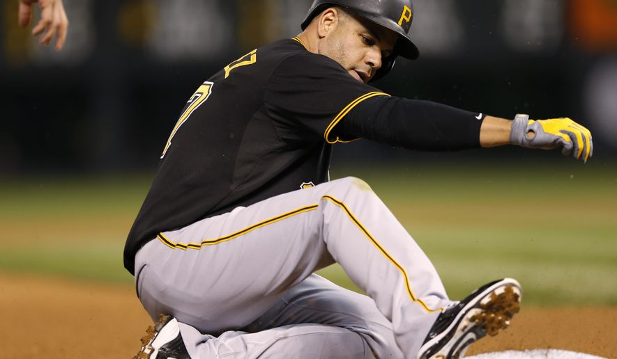 Pittsburgh Pirates' Aramis Ramirez slides safely into third base with an RBI triple off Colorado Rockies starting pitcher Chris Rusin during the fourth inning of a baseball game Tuesday, Sept. 22, 2015, in Denver. (AP Photo/David Zalubowski)