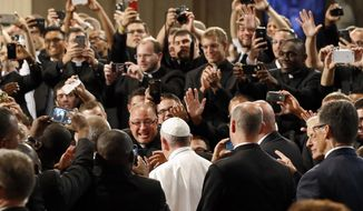 Seminarians greet Pope Francis, bottom center, as he walks into the Basilica of the National Shrine of the Immaculate Conception in Washington, Wednesday, Sept. 23, 2015, before holding a mass to canonize Junipero Serra. (AP Photo/Patrick Semansky, Pool)
