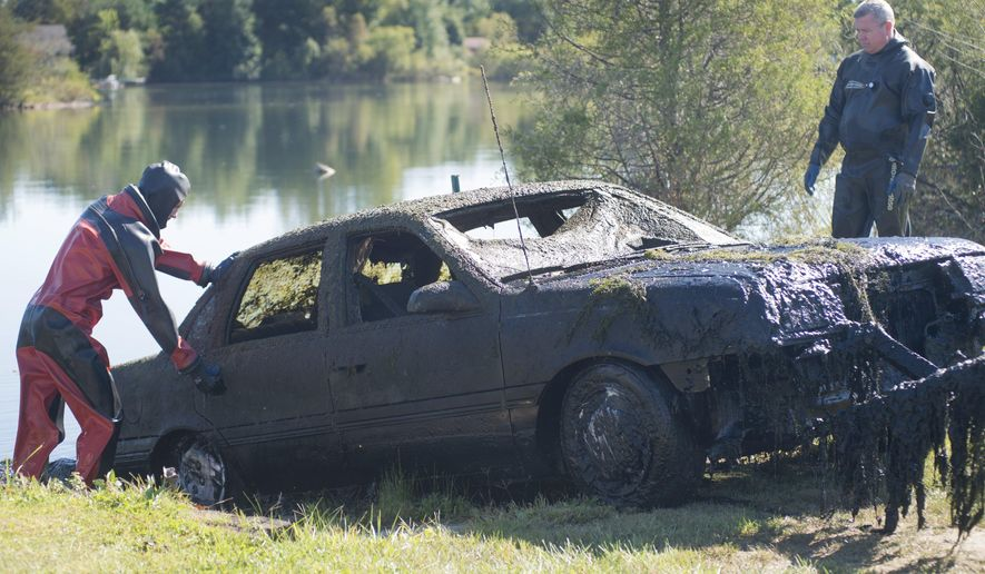 Saginaw County Sheriff's Department Dive Team divers Ron Maynard, left, and Mike Fabish inspect a car that was discovered by people fishing in a pond  in Brady Township, Mich., on Tuesday, Sept. 22, 2015. The mud- and plant-covered car was pulled slowly from the water. A search didn't find human remains inside. Authorities are investigating how the car got into the pond.   (Jeff Schrier/The Saginaw News via AP) ALL LOCAL TELEVISION OUT; LOCAL TELEVISION INTERNET OUT; MANDATORY CREDIT