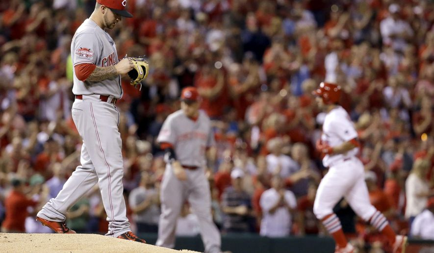Cincinnati Reds relief pitcher Brandon Finnegan, left, steps off the mound as St. Louis Cardinals' Randal Grichuk rounds the bases after hitting a solo home run during the second inning of a baseball game Wednesday, Sept. 23, 2015, in St. Louis. (AP Photo/Jeff Roberson)