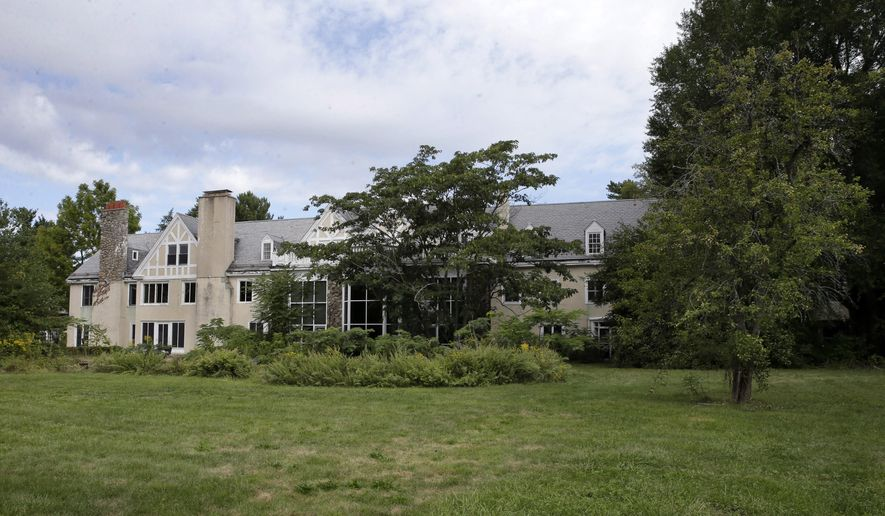 In this Sunday, Sept. 20, 2015 photograph, a portion of the sprawling main mansion of the Duke Farms estate that heiress Doris Duke once called home is seen in Hillsborough Township, N.J. The debate over whether the unoccupied mansion should be demolished will continue this week, when farm officials and community groups opposed to the plan continue to make their case before a local historical board. (AP Photo/Mel Evans)