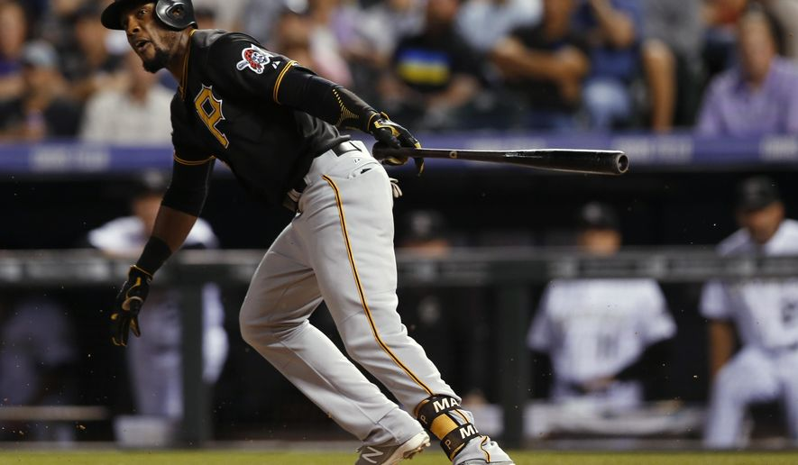 Pittsburgh Pirates' Starling Marte follows through on an RBI single off Colorado Rockies starting pitcher Chris Rusin during the fourth inning of a baseball game Tuesday, Sept. 22, 2015, in Denver. (AP Photo/David Zalubowski)