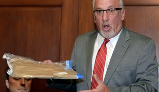 Thomas J. Eoannou, a lawyer for a woman alleging she was sexually assaulted by Chicago Blackhawks forward Patrick Kane, holds up what he says is an empty evidence bag that was improperly left in the doorway of the woman's mother's home, during a news conference, Wednesday, Sept. 23, 2015, in Buffalo, N.Y. Eoannou said the bag at one point contained the rape kit used when the woman reported that she had been assaulted.   (AP Photo/Gary Wiepert)