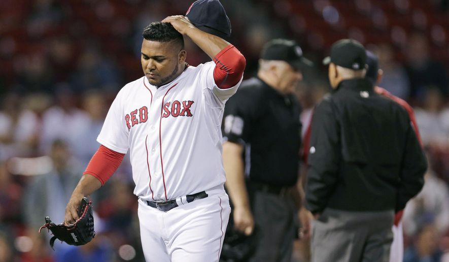 Boston Red Sox relief pitcher Jean Machi scratches his head as he heads for the clubhouse after getting ejected for almost hitting Tampa Bay Rays batter Steven Souza Jr. during the ninth inning of a baseball game at Fenway Park in Boston, Wednesday, Sept. 23, 2015. (AP Photo/Charles Krupa)