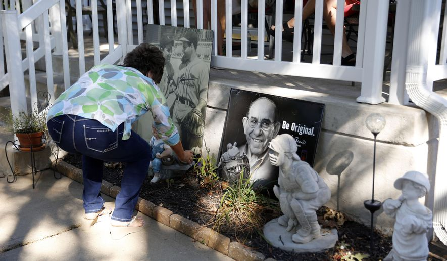 Barbara Berra places a baseball at a memorial outside the boyhood home of her uncle, baseball Hall of Fame catcher Yogi Berra, Wednesday, Sept. 23, 2015, in St. Louis. Berra, who helped the New York Yankees to 10 World Series championships has died Tuesday of natural causes at his home in New Jersey, according to Dave Kaplan, the director of the Yogi Berra Museum.  He was 90.(AP Photo/Jeff Roberson)