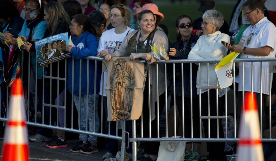 A woman holds an image of the Virgin Mary as she and others gather on Pope Francis parade route along the Ellipse near the White House in Washington, Wednesday, Sept. 23, 2015. (AP Photo/Carolyn Kaster)