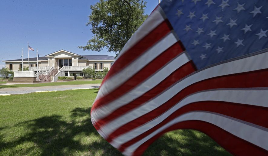 An American flag flies in front of a new courthouse annex, built with recovery funds from Hurricane Rita, which hit nearly ten years ago, in Cameron, La., Tuesday, Sept. 15, 2015. A decade after Hurricane Rita, Cameron Parish in coastal, southwest Louisiana still bears the scars of her wrath. Thursday, Sept. 24, 2015 is the anniversary of Hurricane Rita.  (AP Photo/Gerald Herbert)