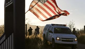 An American flag on a nearby resident's home waves in the breeze on Dec. 15, 2010, near a U.S. Border Patrol truck blocking the road leading to a search area near where agent Brian Terry, 40, was killed northwest of Nogales, Ariz. (Arizona Daily Star via Associated Press)