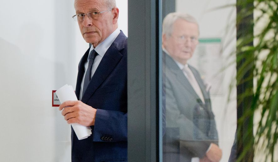 Berthold Huber, acting head of Volkswagen's supervisory board, left, and supervisory board member Wolfgang Porsche, right,  arrive for a statement announcing that CEO Martin Winterkorn stepped down amid an emissions scandal in the company's headquarters in Wolfsburg, Germany, Wednesday, Sept. 23, 2015. (Julian Stratenschulte/dpa via AP)