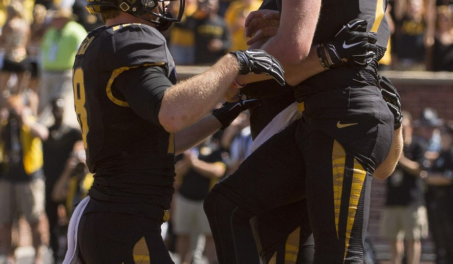 Missouri quarterback Maty Mauk, left, celebrates with teammate Wesley Leftwich, left, after Mauk scored a touchdown during the third quarter of an NCAA college football game against Connecticut, Saturday, Sept. 19, 2015, in Columbia, Mo. Missouri won the game 9-6.  (AP Photo/L.G. Patterson)