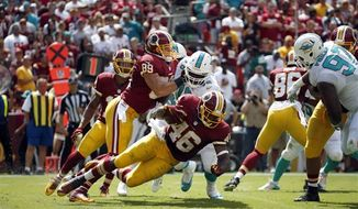 Washington Redskins running back Alfred Morris (46) tries to get away from Miami Dolphins defensive end Terrence Fede (78) as he is blocked by tight end Derek Carrier (89) during the first half of an NFL football game Sunday, Sept. 13, 2015, in Landover, Md. (AP Photo/Evan Vucci)