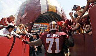 Washington Redskins tackle Trent Williams (71) greets fans as he prepares to enter the field before an NFL football game against the Miami Dolphins, Sunday, Sept. 13, 2015, in Landover, Md. (AP Photo/Alex Brandon)