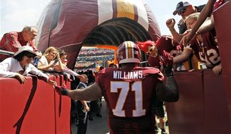 Washington Redskins tackle Trent Williams (71) greets fans as he prepares to enter the field before an NFL football game against the Miami Dolphins, Sunday, Sept. 13, 2015, in Landover, Md. (AP Photo/Alex Brandon)  **FILE**