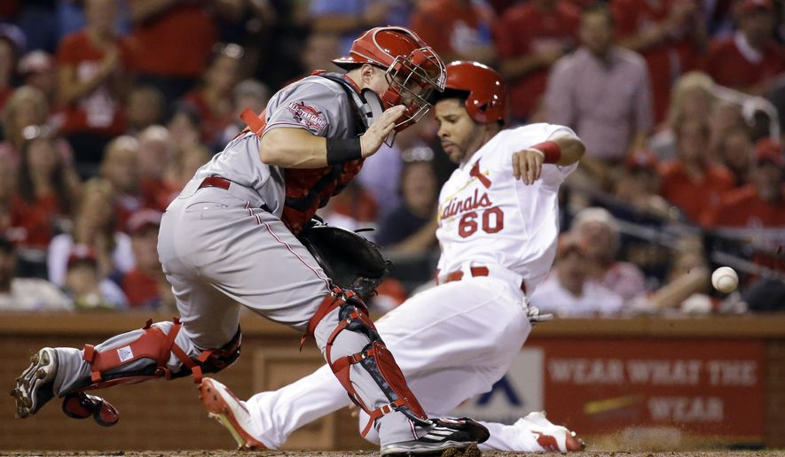 Cincinnati Reds catcher Tucker Barnhart, left, waits for the throw as St. Louis Cardinals' Tommy Pham scores on a double by Matt Holliday during the third inning of a baseball game on Wednesday, Sept. 23, 2015, in St. Louis. (AP Photo/Jeff Roberson)