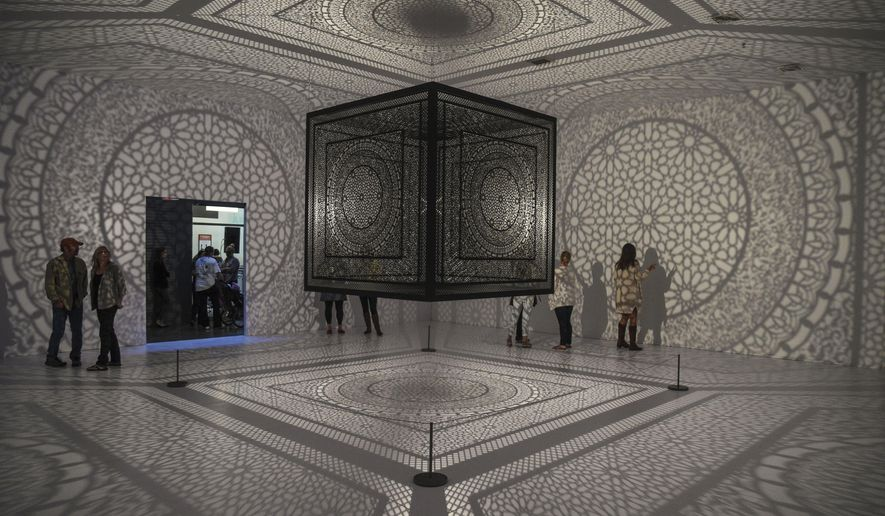 "People admire a replica of the 2014 ArtPrize winner, Pakistani-American artist Anila Quayyum Agha's piece, ""Intersections,"" on Saturday, Sept. 19, 2015, at the kick-off for ArtPrize Seven 2015 at the ArtPrize Hub Headquarters in Grand Rapids, Mich. (Taylor Ballek/ MLive.com via AP)"