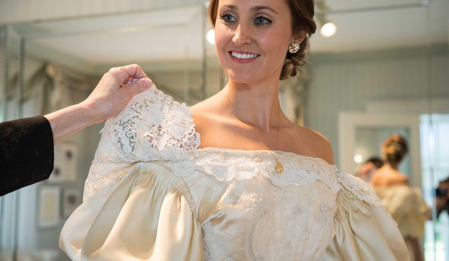 Abigail Kingston tries on a wedding dress  that has been passed down in her family for over 100 years and will be the 11th bride to wear it on Tuesday, Sept. 22, 2015 in Bethlehem, Pa.  Thanks to 200 hours of painstaking restorations by Wilson Borough bridal designer Deborah LoPresti's salon, Kingston will don the dress on her wedding day on Oct. 17.  (Kelly McEwan/The Express-Times via AP) MANDATORY CREDIT