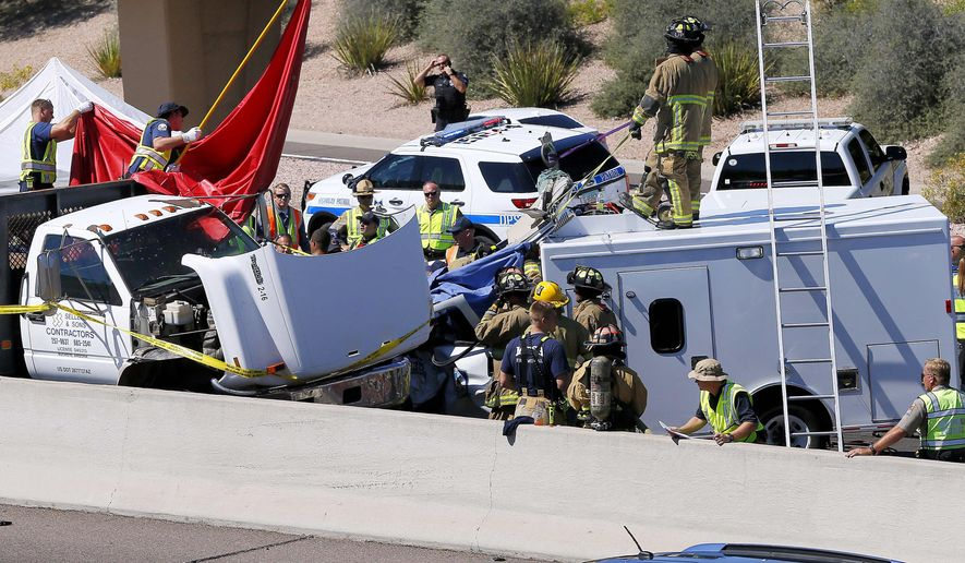 Fire and police crews work to remove the driver from a wrecked police transport, Wednesday, Sept. 23, 2015, in Mesa, Ariz. Authorities say a police transport van crashed into another vehicle on U.S. 60 near the Loop 101. (AP Photo/Matt York)