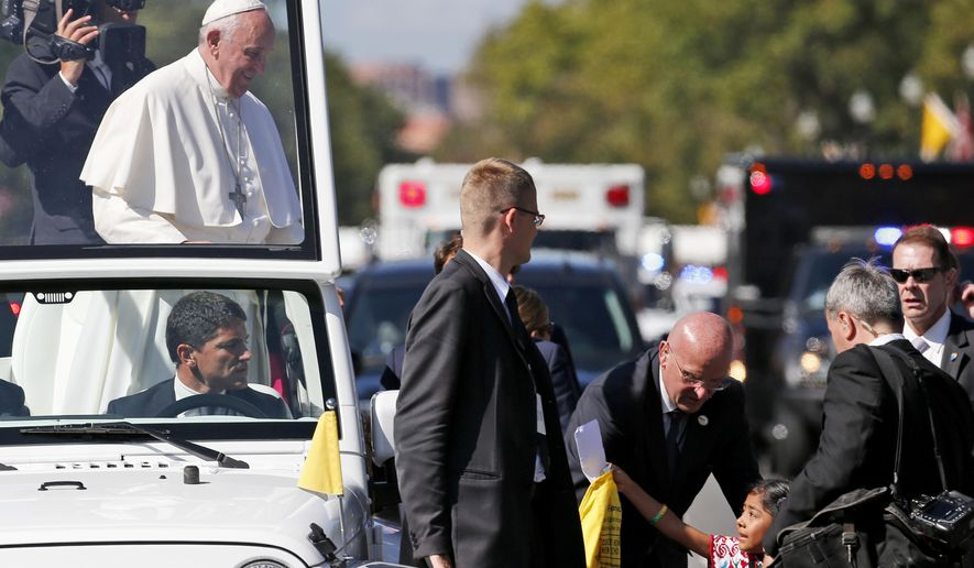 Sophie Cruz, 5, of suburban Los Angeles reaches to give Pope Francis a letter and t-shirt during a parade in Washington, Wednesday, Sept. 23, 2015. The massive security apparatus protecting Pope Francis on his historic, six-day trip to the U.S. got its first test Wednesday as the 5-year-old girl with a gift for the pontiff made her way through a security barrier and onto his parade route. (AP Photo/Alex Brandon, Pool)