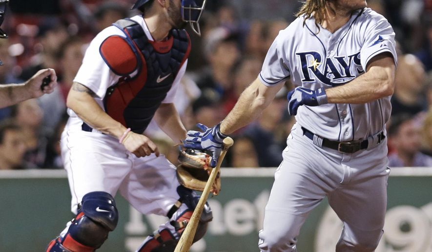 Tampa Bay Rays' John Jaso, right, watches his two-RBI double off Boston Red Sox relief pitcher Tommy Layne during the eighth inning of a baseball game at Fenway Park in Boston, Wednesday, Sept. 23, 2015. At left is Red Sox catcher Blake Swihart. (AP Photo/Charles Krupa)