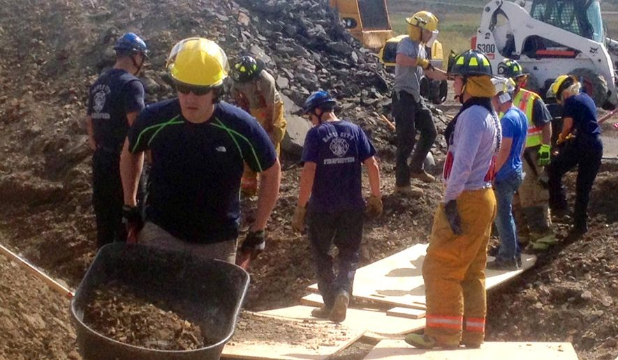 Crews work to stabilize and remove dirt where two workers were trapped after a trench they were digging for a sewer collapsed Wednesday, Sept. 23, 2015 in Hermosa, S.D. The men are conscious and talking, but authorities are concerned about crushing injuries that the workers may have suffered. (Chris Huber/The Rapid City Journal via AP) TV OUT; MANDATORY CREDIT BEST