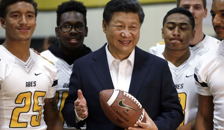 Chinese President Xi Jinping poses with football players and a football he was given during a visit to Lincoln High School, Wednesday, Sept. 23, 2015, in Tacoma, Wash. Xi is on the second of a three-day trip to Seattle before traveling to Washington, D.C., for a White House state dinner on Friday. (AP Photo/Elaine Thompson)