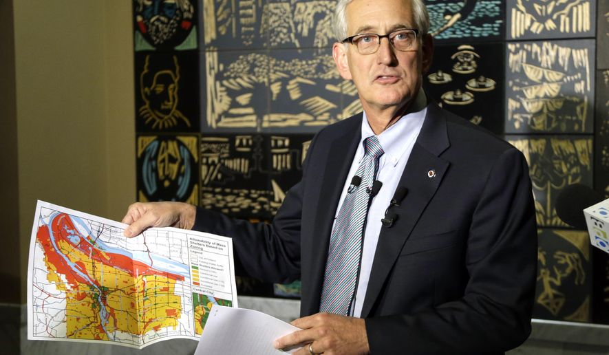 Portland Mayor Charlie Hales holds up a city map showing where homeless shelters can and cannot be located at a news conference in Portland, Ore., Wednesday, Sept. 23, 2015.  Hales said Portland needs to quickly address a lack of housing, create more shelters and is seeking an emergency declaration that will allow the city to waive zoning codes and convert city-owned buildings into shelters through an expedited process. Red on the map indicates where shelters cannot be located.(AP Photo/Don Ryan)