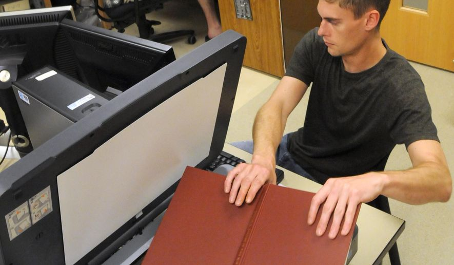 ADVANCED FOR RELEASE SATURDAY, SEPTEMBER 26, 2015 Minnesota State University, Mankato graduate students Josh Anderson (foreground) and Andy Brown work on a comprehensive archaeological database Sept. 1, 2015 at the university. The first-of-its-kind effort is massive and is expected to take years to finish. (Pat Christman/Mankato Free Press via AP)