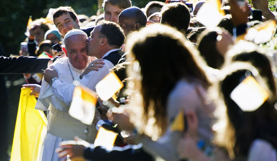 A man kisses Pope Francis while he greets well-wishers outside the Apostolic Nunciature, the Vatican's diplomatic mission in Washington, Wednesday, Sept. 23, 2015, prior to his departure to the White House where President Barack Obama will host a state arrival ceremony.  (AP Photo/Cliff Owen)