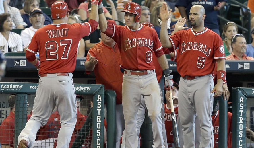 Los Angeles Angels Taylor Featherston (8) and Albert Pujols (5) welcome Mike Trout (27) back to the dugout after he scored on a David Freese two-run double against the Houston Astros in the eighth inning of a baseball game Wednesday, Sept. 23, 2015, in Houston. (AP Photo/Pat Sullivan)