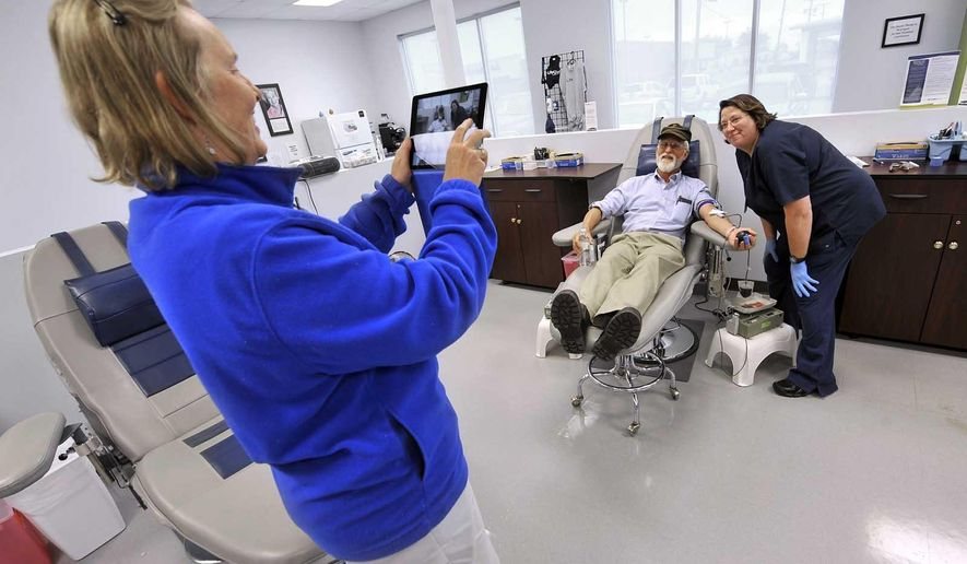 In this Wednesday, Sept. 23, 2015 photo, John Ball, of Charlottesville, Va., gets his picture taken by his wife, Alyson Ball, at left, with donor services technician Elaine Murman at the Life Serve Blood Center in Fort Dodge, Iowa. The donation completed Ball's quest to donate blood at least once in all 50 states. (Hans Madsen/The Messenger via AP)