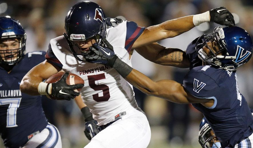 Penn's Justin Watson gets his facemask pulled by Villanova's Malik Reaves during the first quarter of an NCAA college football game Thursday, Sept. 24, 2015, in Philadelphia. (Yong Kim/The Philadelphia Inquirer via AP)