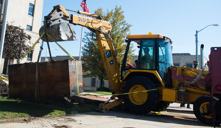 In this photo taken Wednesday, Sept. 23, 2015, Tim Fedek, Bay County Building and Grounds, uses a backhoe to lift a 50-year-old time capsule onto a truck at Bay County Building's southwest lawn  in Bay City, Mich. (Yfat Yossifor/The Bay City Times via AP) LOCAL TELEVISION OUT; LOCAL INTERNET OUT; MANDATORY CREDIT