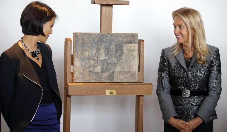 "French Minister of Culture and Communication Fleur Pellerin, left, and Jane D. Hartley, U.S. Ambassador to France, right, pose next to ""La Coiffeuse,"" or The Hairdresser, a $ 15 million Picasso painting, found in New Jersey, during a presentation at Beaubourg Pompidou Center Museum in Paris, France, Thursday, Sept. 24, 2015. This Picasso artwork, painted in 1911, is going back on display in a Paris Museum after it disappeared from a French storage room more than a decade ago, then turned up in a package from Belgium to New York last year. (AP Photo/Francois Mori)"