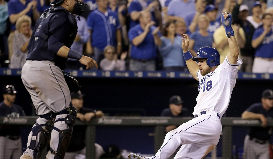 Kansas City Royals' Ben Zobrist (18) slides home past Seattle Mariners catcher Jesus Sucre to score on a two-run single by Lorenzo Cain during the sixth inning of a baseball game Thursday, Sept. 24, 2015, in Kansas City, Mo. (AP Photo/Charlie Riedel)